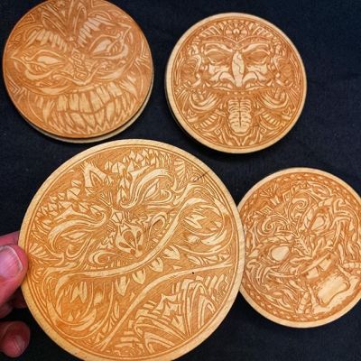 I had these tiki coasters made from my art last year from a laser engraver. I'm at a convention and close to getting rid of the last of the batch. Should I reprint these or come up with new designs? Any ideas of a new theme?#tikiartist #tiki #woodart #beachart