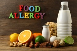 "common food allergens on wooden background with the words ""food allergy"""