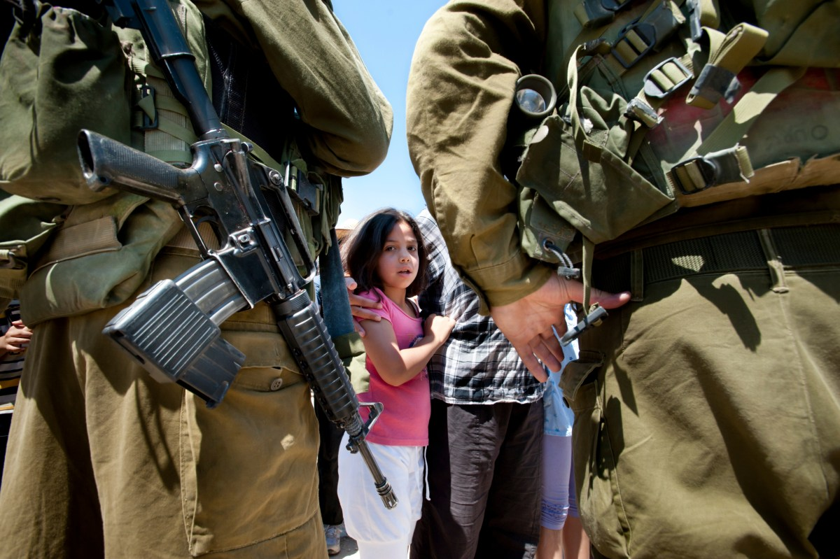 """Al-Walaja, Occupied Palestinian Territories - August 27, 2011: A Palestinian girl confronts Israeli soldiers in a protest against the encirclement of the West Bank town of Al-Walaja by the Israeli separation barrier."""
