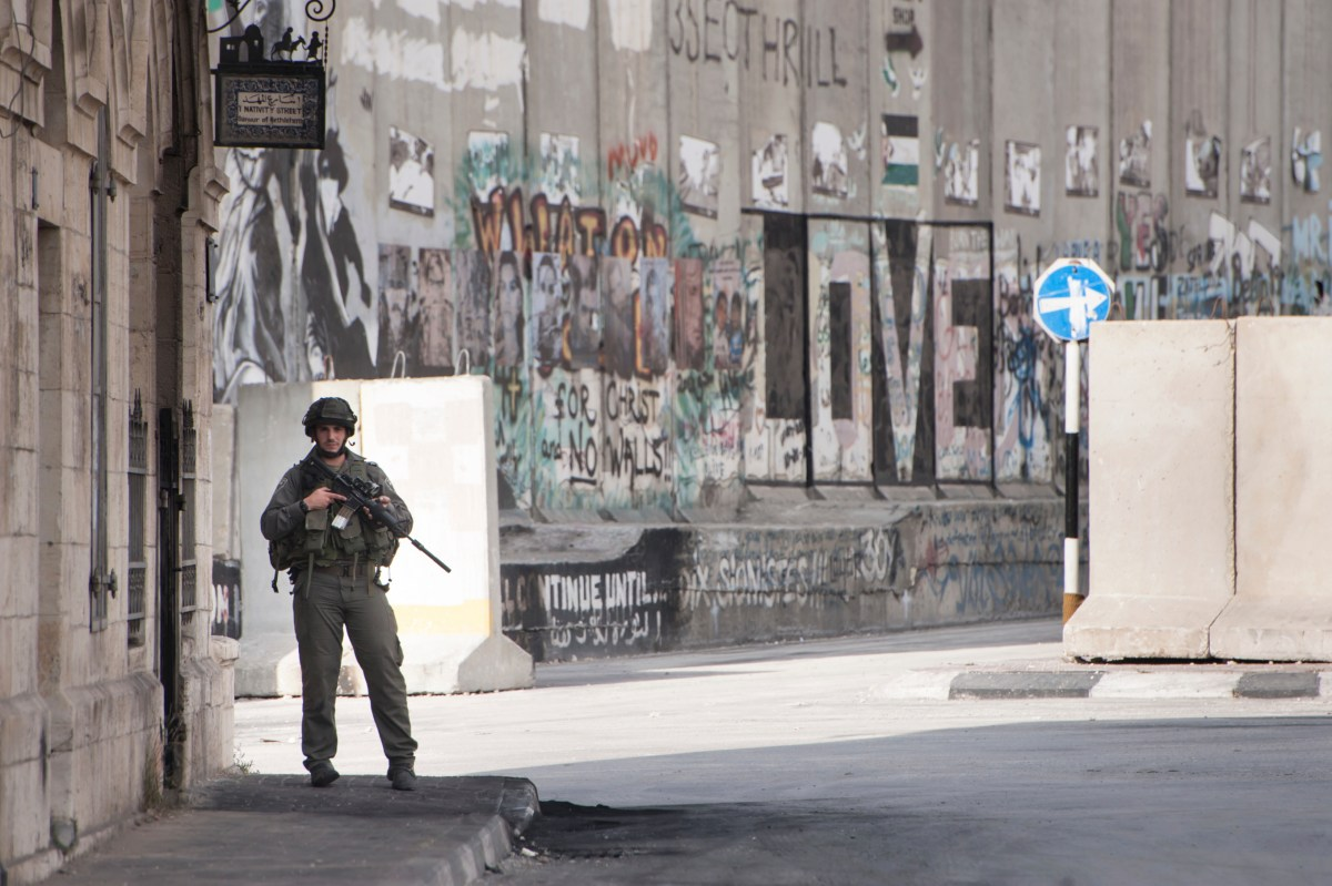 Bethlehem, Occupied Palestinian Territories - November 20, 2012: An Israeli soldier occupies a street corner near the Israeli separation wall in Bethlehem, West Bank.