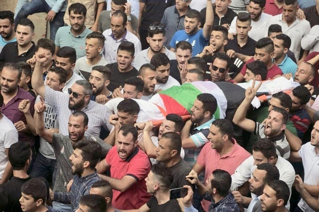 Palestinians carry the body of 48-year-old mother of eight, Aisha Rabi, who died of her wounds after the car she was travelling in with her husband was hit by stones, during her funeral in the West Bank village of Bidya, near Salfit, on October 13, 2018. - An Israeli police spokesman confirmed a car had been hit by stones but did not identify the perpetrators. He said an investigation was underway but did not give further details. (Photo by JAAFAR ASHTIYEH / AFP)