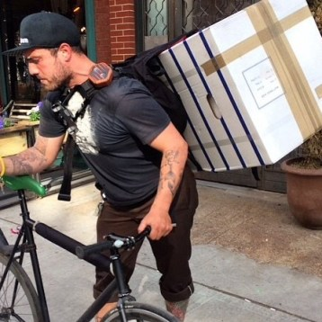 A man delivering a mattress in a box on a bicycle