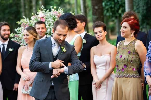 Noivo olha no relógio, ansioso pela entrada da noiva que está atrasada irmã olha e sorri ao fundo