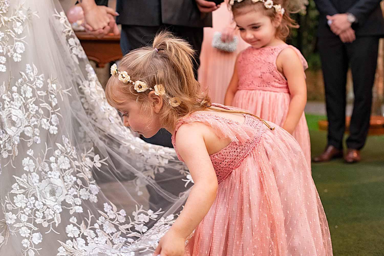 Linda fotografia de criança daminha ajeitando o vestido da noiva