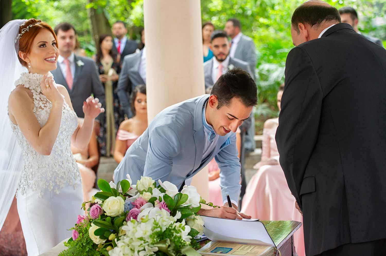 Casamento no iate clube de santos em são paulo de dia noivo assinando a certidão e noiva sorrindo super feliz