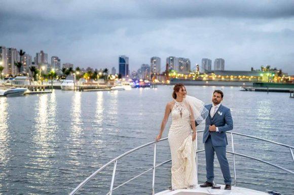 Noivo observa noiva enquanto ela observa o horizonte do deck da lancha próximo ao iate clube de santos no guarujá