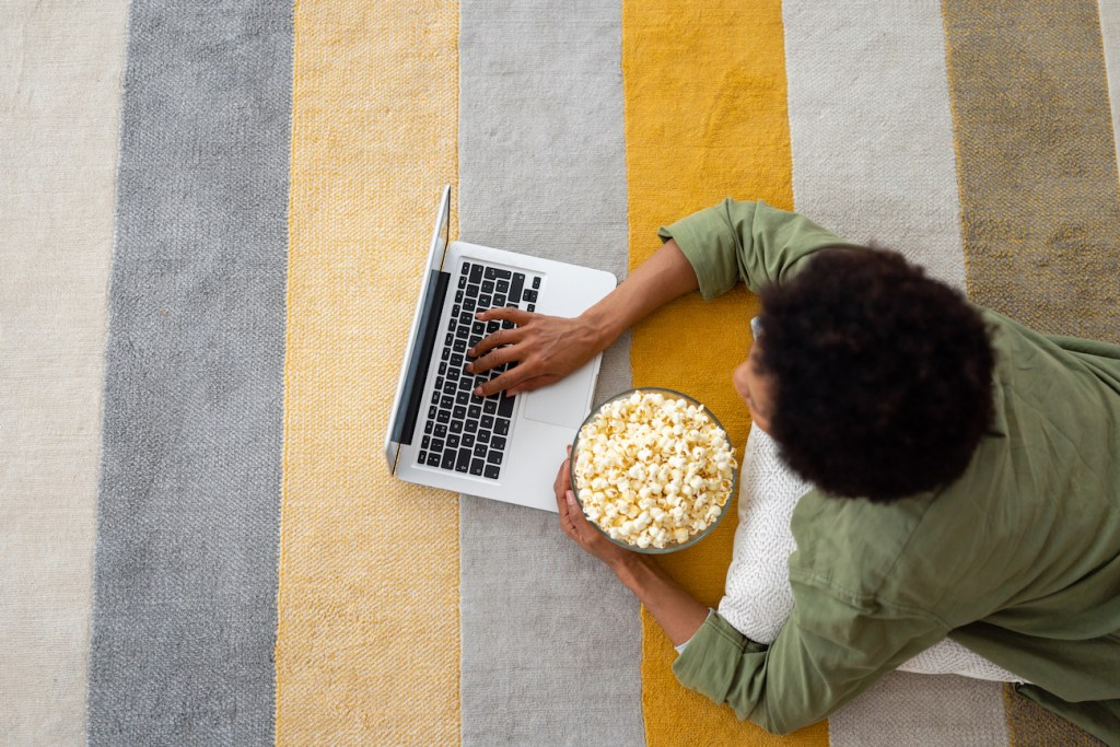 Top view of African American adult woman laying on ground and using laptop at home