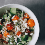 Low FODMAP Quinoa salad topped with tomato, cucumber, and feta cheese