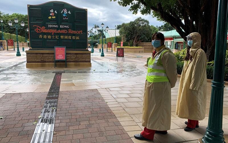 Funcionários usando máscaras são vistos do lado de fora da Disneyland Hong Kong, fechada, no domingo (26) — Foto: Reuters/James Pomfret