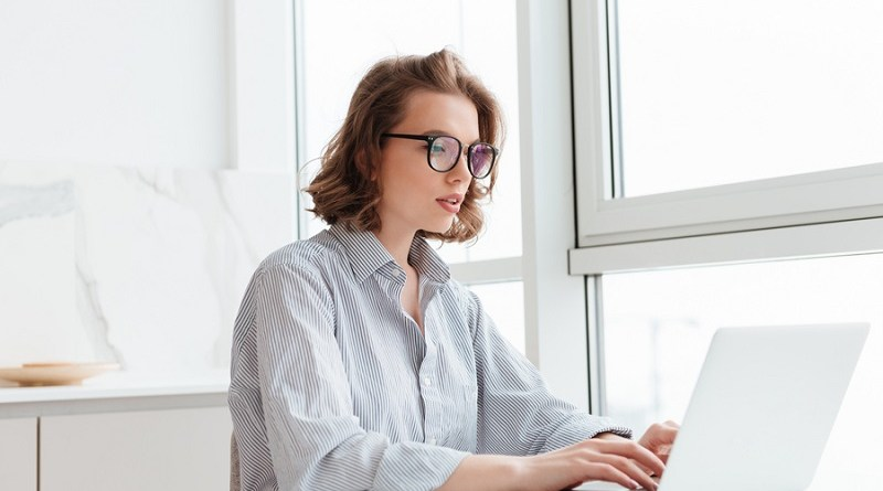 Photo of young concentrated woman in striped shirt using laptop while siting at table in light apartment