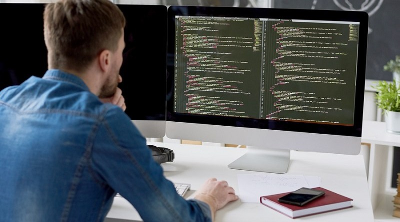 Rear view of concentrated thoughtful male programmer viewing computer language code on computer monitor while working on new program in modern office