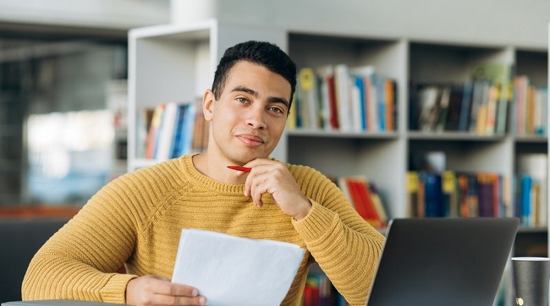Portrait of young adult hispanic male freelancer or student is looking at the camera with smile. Attractive business man sits at the work desk, making notes, learning online