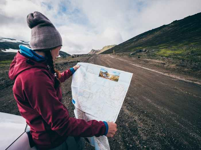 woman with map on side of road while driving in iceland