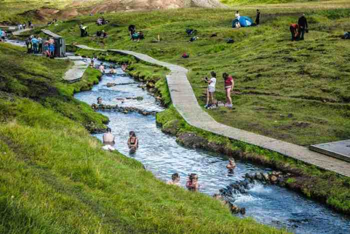 many people bathing in the river at Reykjadalur Hot Springs
