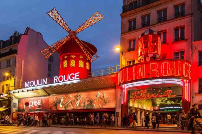 Moulin Rouge with the windmill lit in red light at night, Paris in a Day