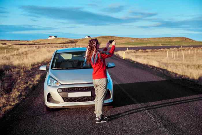woman using phone for photos next to iceland car hire