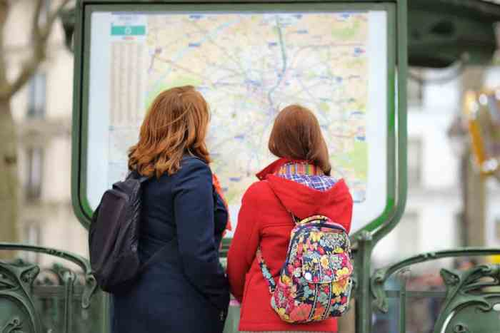 women looking at a map of the paris metro