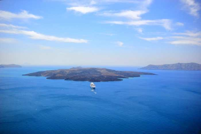 Photo of island formed by volcano you could visit during your Greece honeymoon.