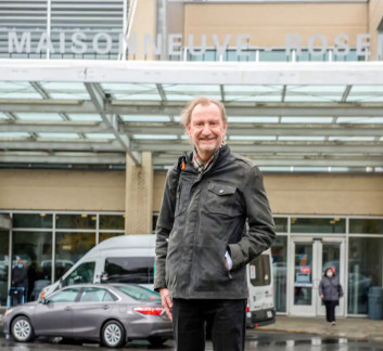 Photo of François Quenot poses in front of the entrance to the Hospital Maisonneuve-Rosemont.