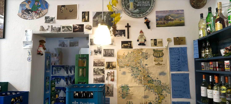 Kassenbereich der Getränkehändlerin mit aufeinander gestapelten Getränkekästen, Bilder an der Wand, einer Landkarte von Italien.