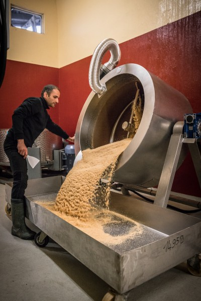 Yuval Königstein tilts the roasted sesame into the large stainless steel pan to cool it down.