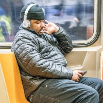 Mann mit Kopfhörer in der Subway.