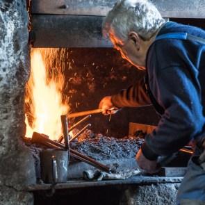 Josef Geisler holt einen Sapie aus der glühenden Steinkohle in der Esse.