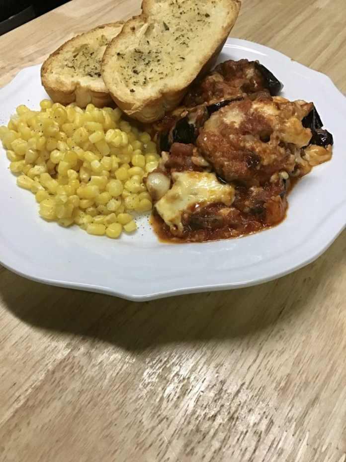 Eggplant Parmesan, sauteed romaine salad, and Italian bread