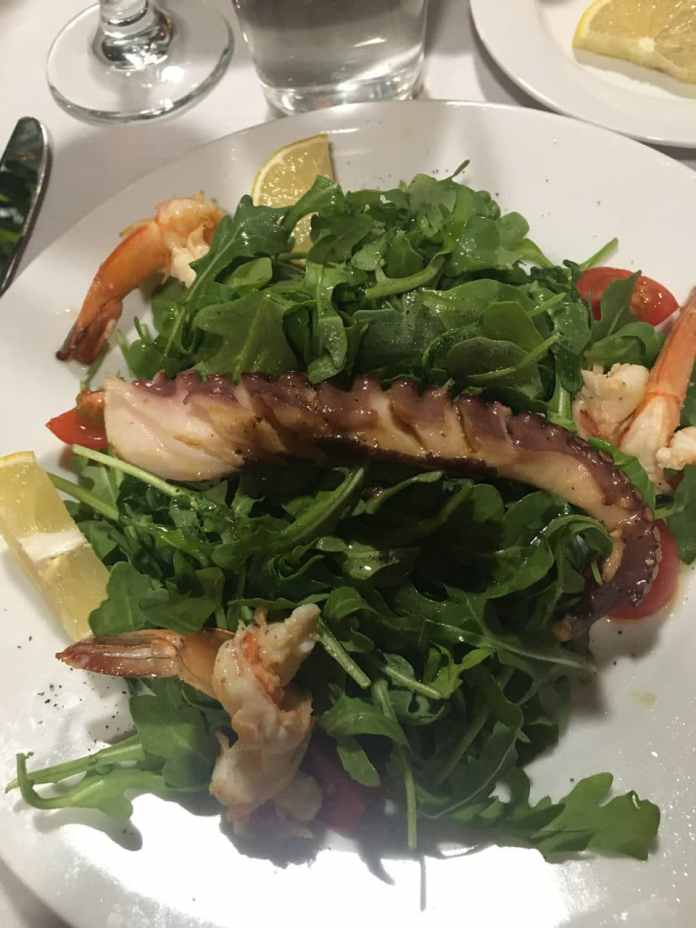 An octopus tentacle was done to perfection served with grilled shrimp and fresh arugula