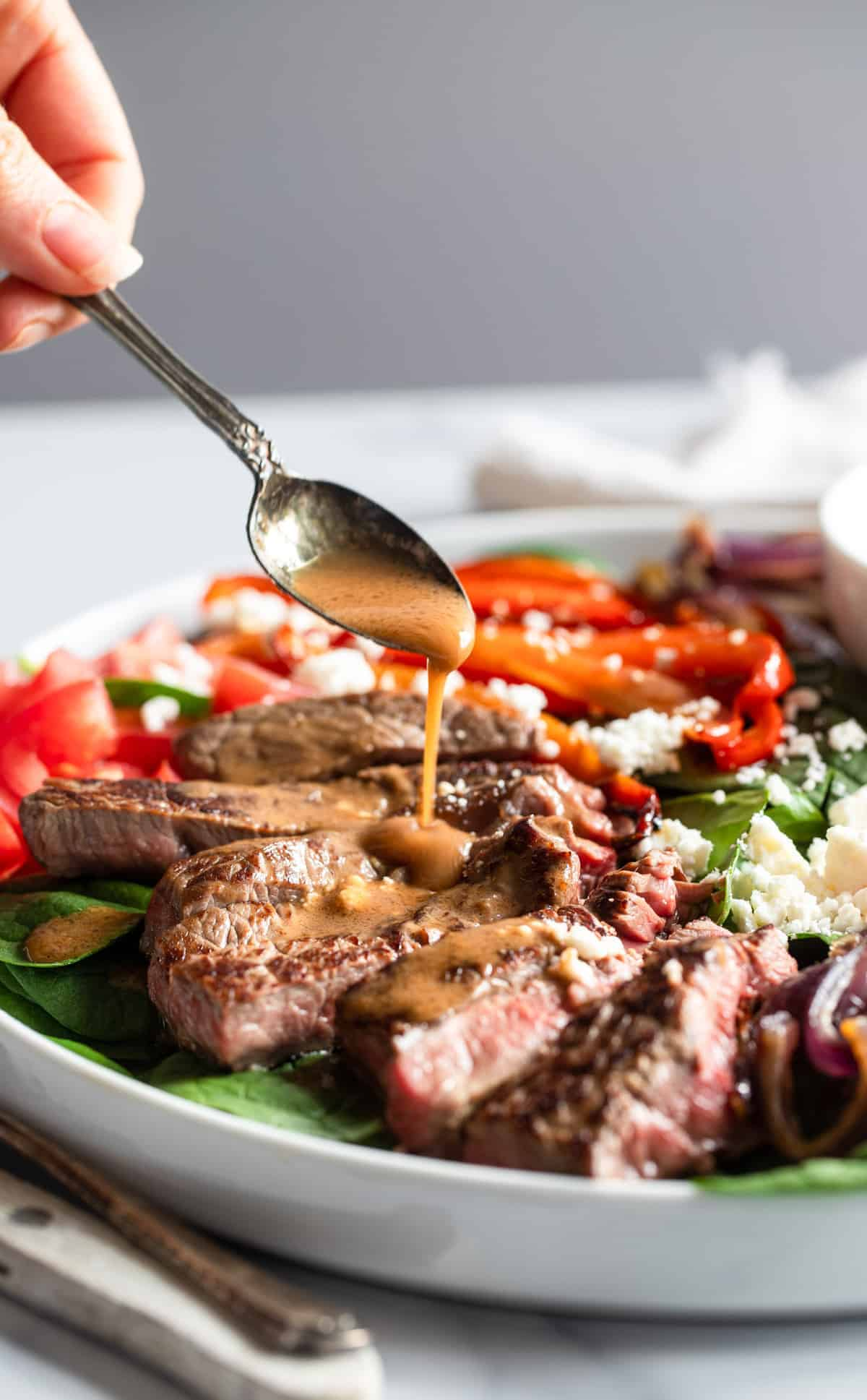 Balsamic Steak Salad being served with sauce