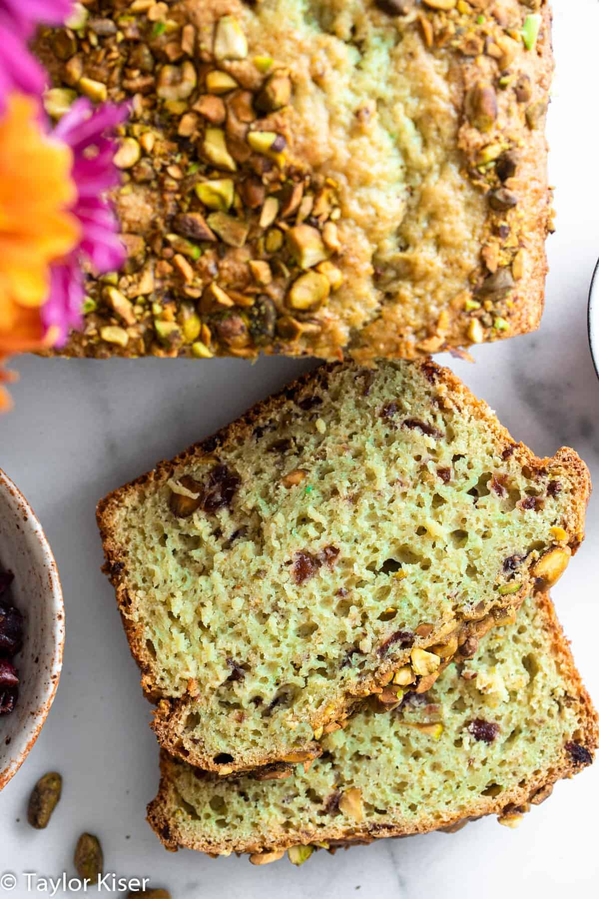 sliced green cranberry pistachio bread on a table