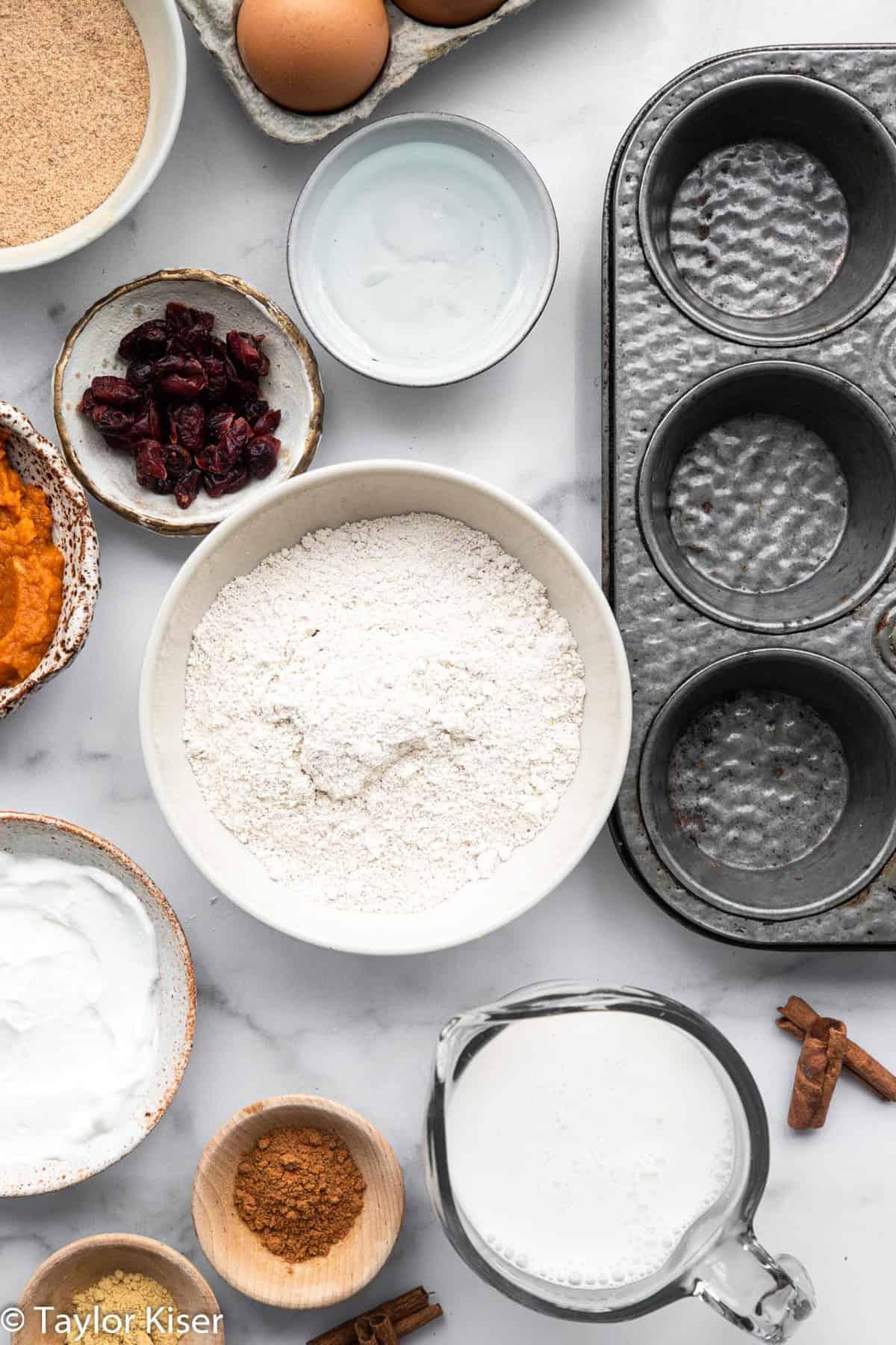 Ingredients to make gluten free pumpkin muffins in bowls