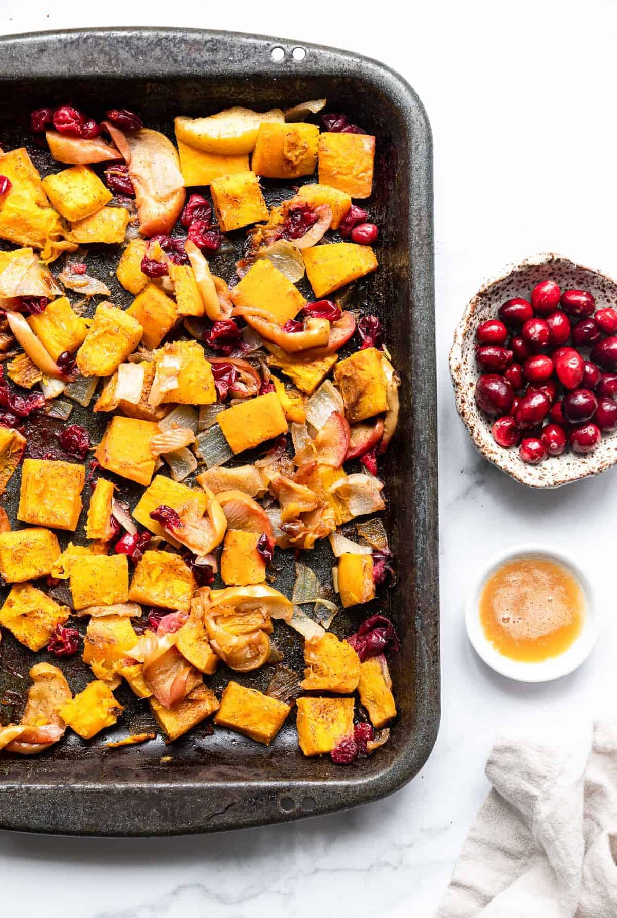 oven roasted pumpkin on a baking sheet with cranberries