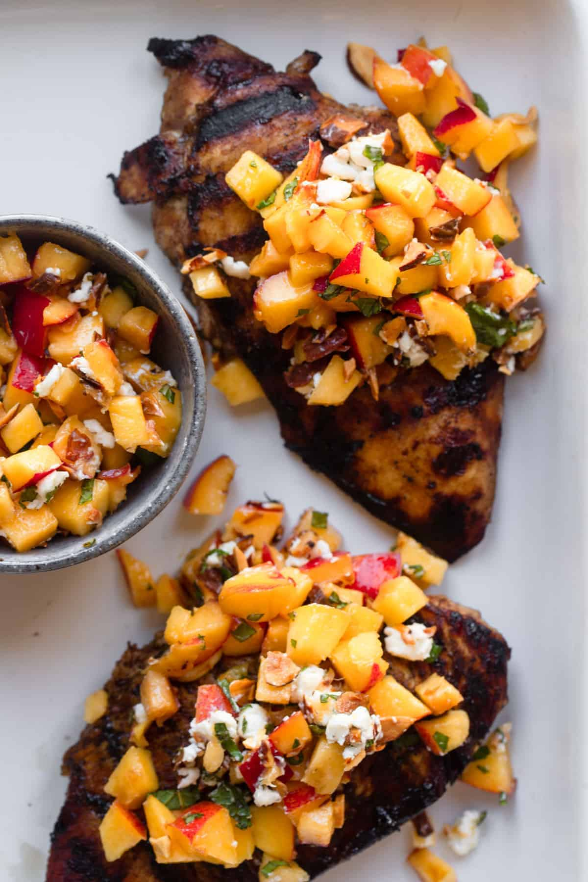 Nectarine Fruit Salsa on chicken on a plate with salsa on the side