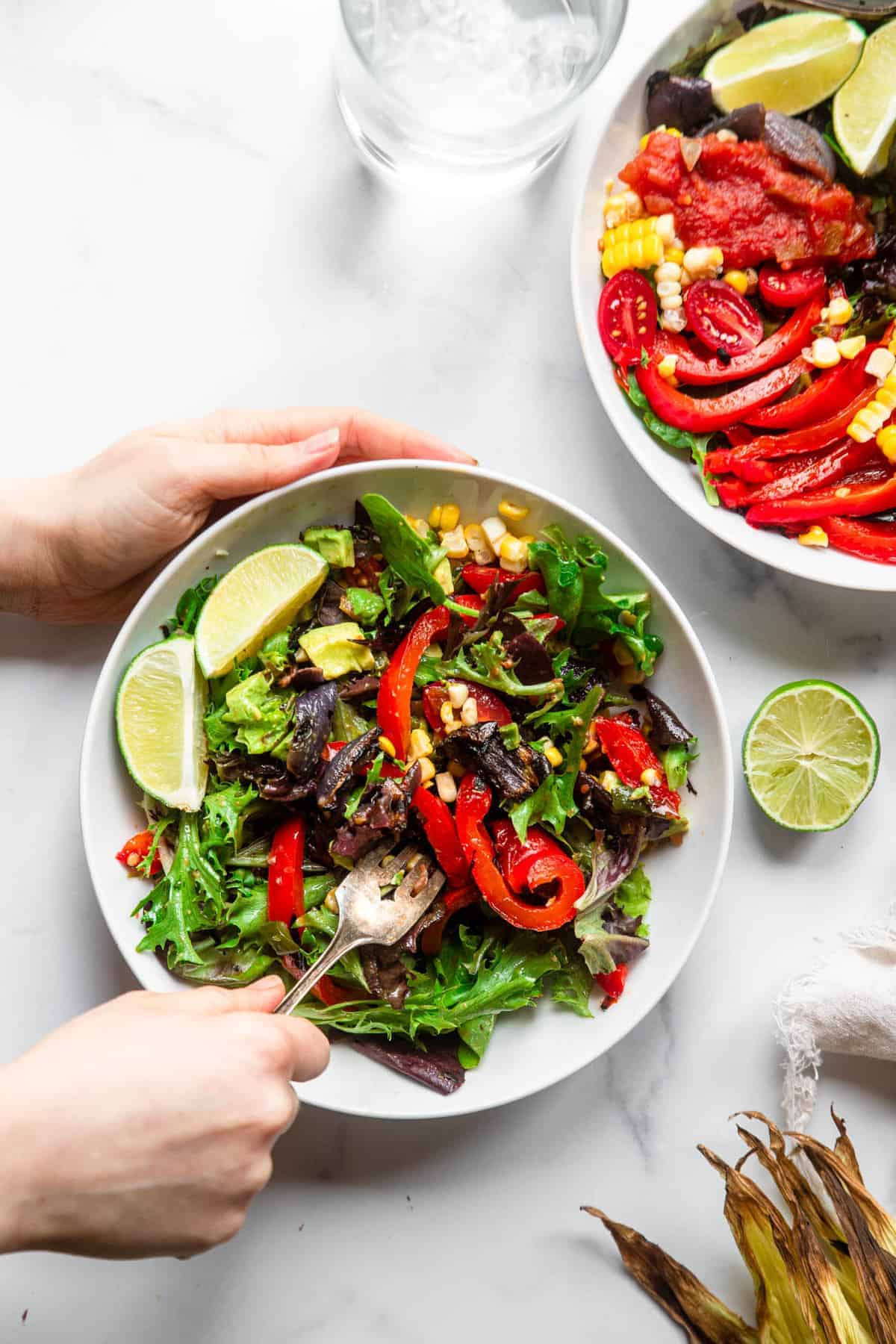 mexican grilled corn salad in a bowl with fork and limes