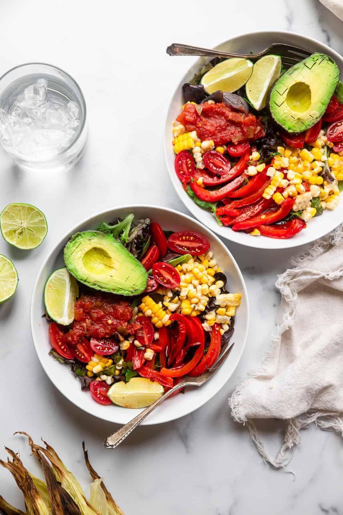mexican grilled corn salad on a table with water and limes