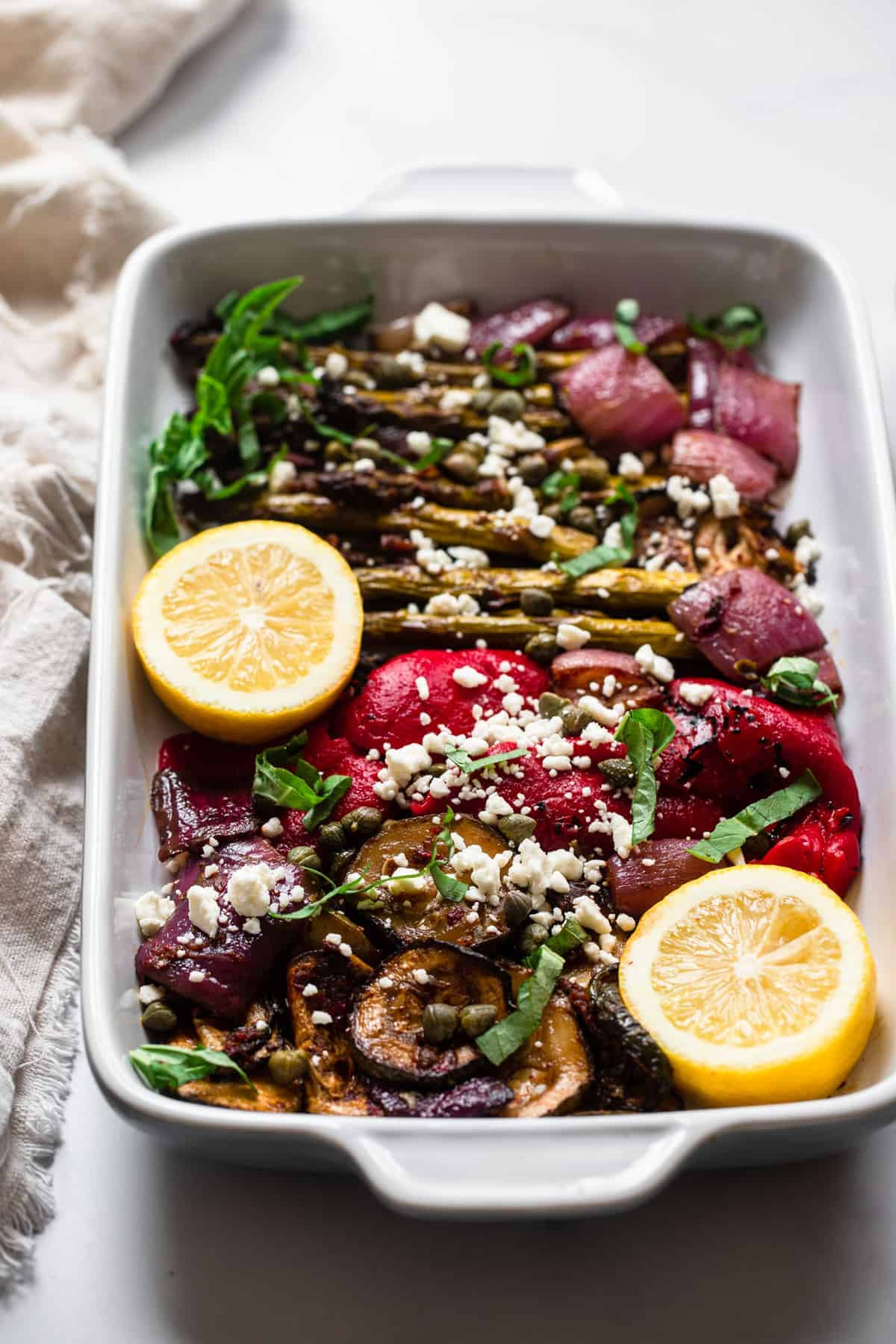 Balsamic grilled vegetable salad in a baking dish with lemon on top