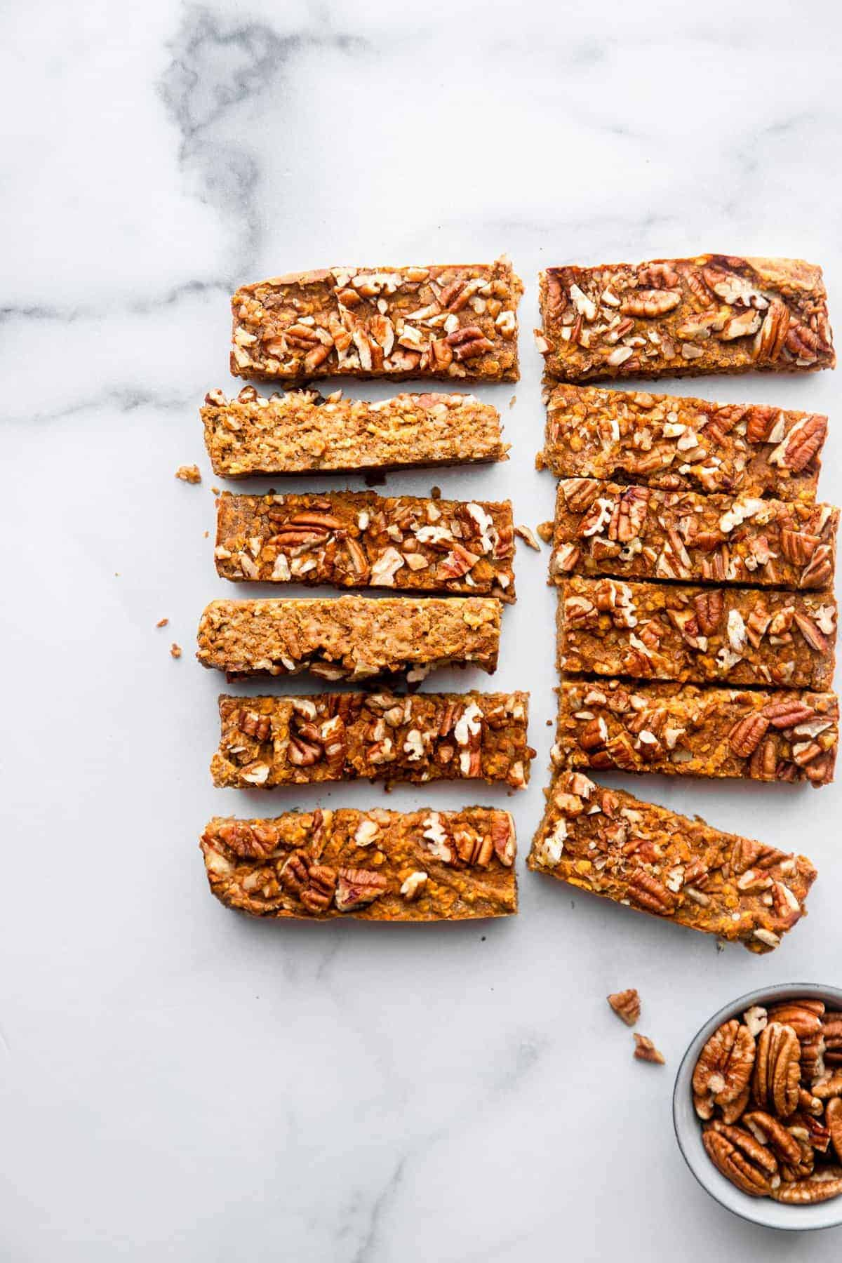 homemade pumpkin protein bars on a table with pecans on the side