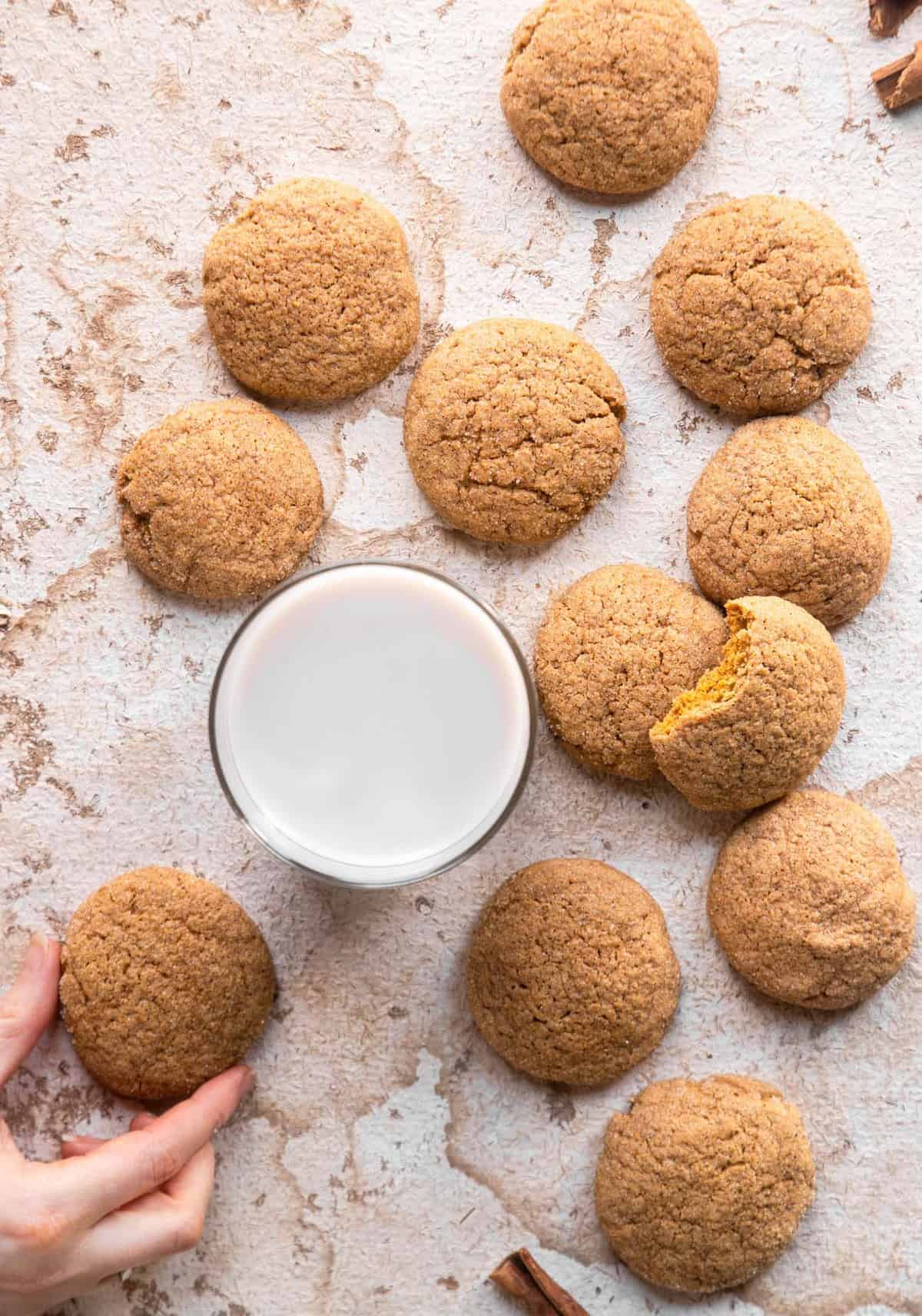 pumpkin sugar cookies on a counter with a glass of milk on the side