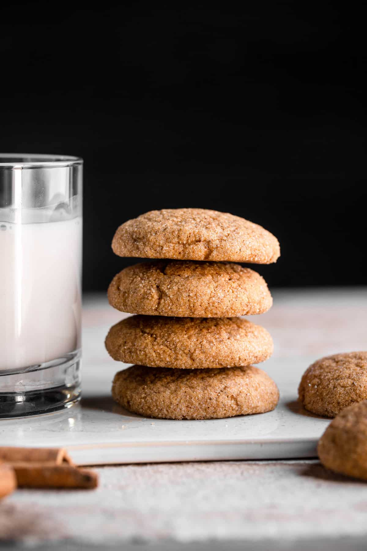 four stacked pumpkin sugar cookies with a glass of milk