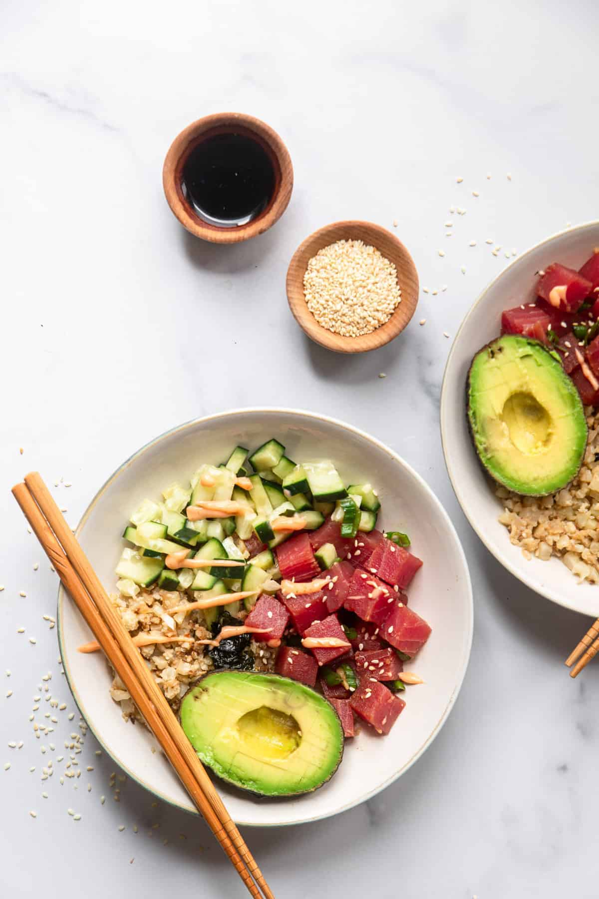 low carb poke bowl on a table with sesame seeds and sauce on the side