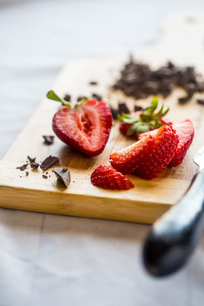 strawberries on a cutting board with chocolate for vegan smoothie bowl