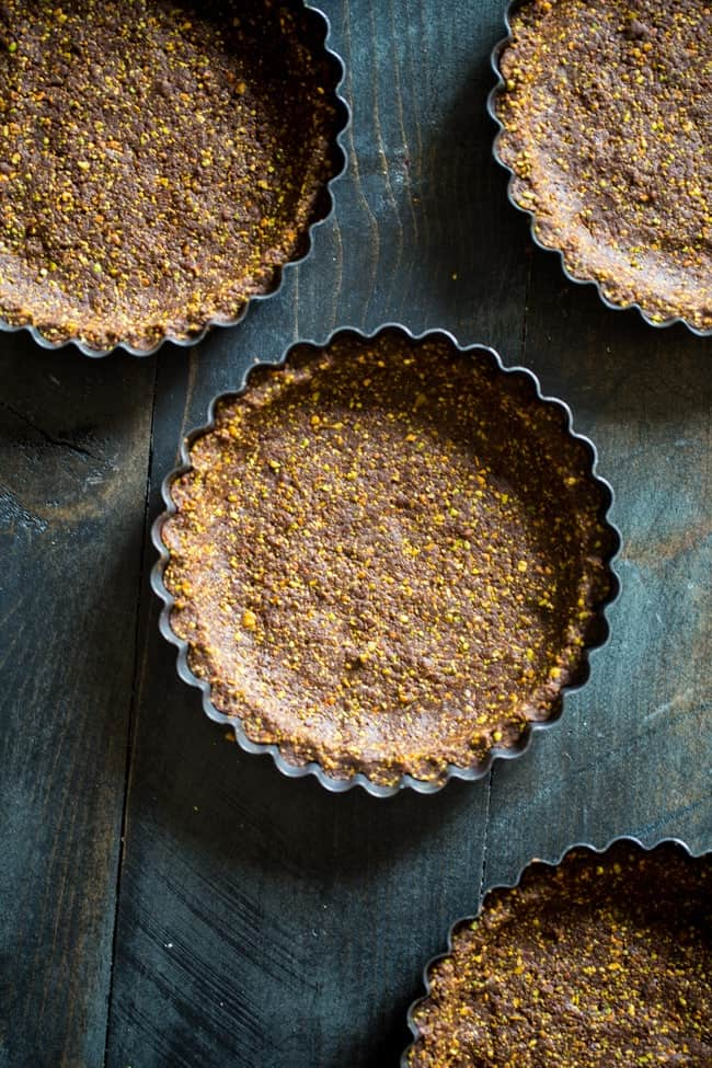 6 Ingredient Paleo and Vegan Raw Chocolate Pistachoo Tarts - This vegan tart is made with only 6 ingredients! It's a healthy, gluten free and paleo dessert that is easy to make! Perfect for Christmas! | Foodfaithfitness.com | @FoodFaithFit