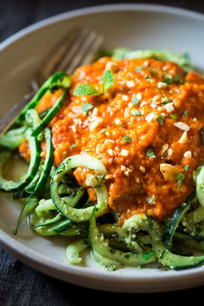 Vegan Lentil Coconut Curry with Cashew Cilantro Pesto Cucumber Noodles - Spiralized cucumbers are mixed with a flavorful pesto and then topped with creamy lentil coconut curry for a healthy, vegan friendly, weeknight meal!   Foodfaithfitness.com   @FoodFaithFit