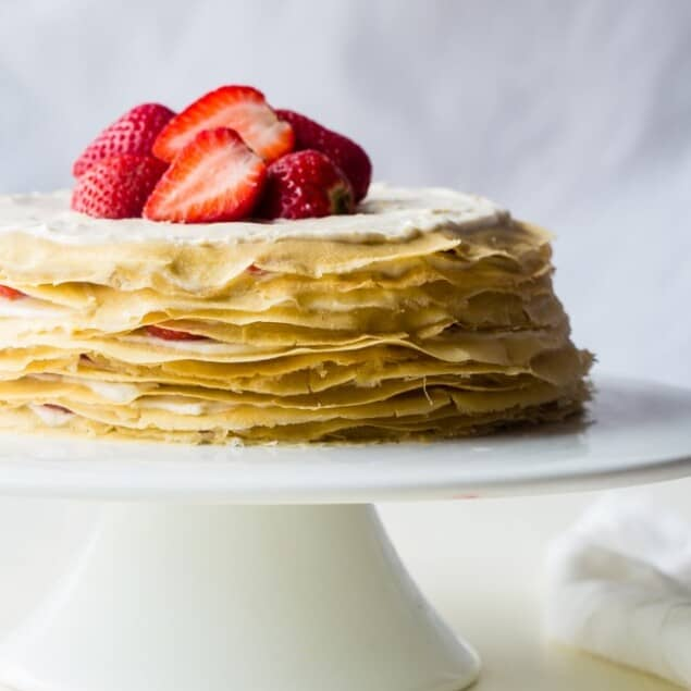 Strawberry Lemon Paleo Crepe Cake with Coconut Cream - This cake is made out of paleo crepes layered with rich, sweet lemon coconut cream and fresh strawberries. It's a gluten free dessert, that's perfect for a spring brunch or Mothers day! | Foodfaithfitness.com | @FoodFaithFit