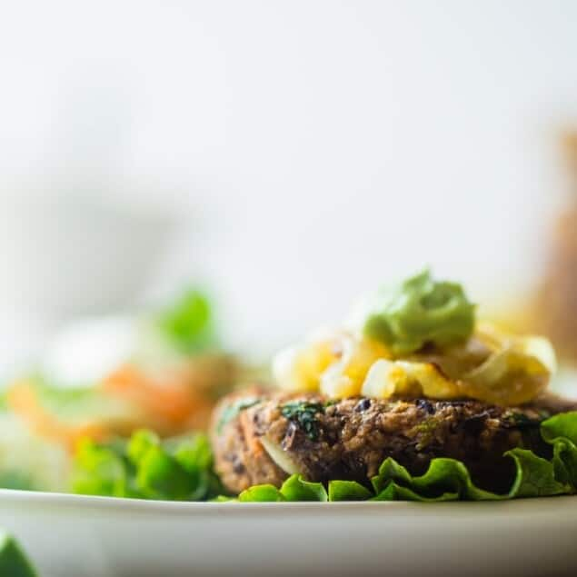Black Bean Power Burger with Avocado Crema - This black bean burger is so tender and juicy you would never know it's meatless! Load it up with caramelized onions and avocado crema for a healthy, gluten free meal that's easy to prepare! | Foodfaithfitness.com | @FoodFaithFit