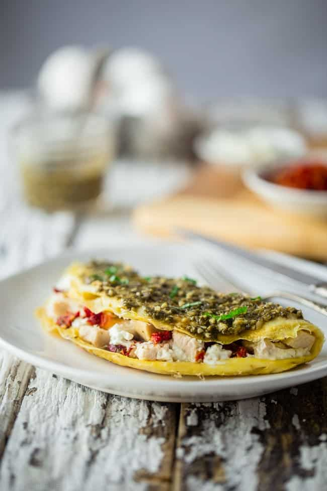 Pesto Chicken Egg White Omelette with Goat Cheese - This quick and easy, protein packed egg white omelette is mixed with chicken, creamy goat cheese and topped with pesto! It's a low carb and gluten free breakfast for busy mornings! | Foodfaithfitness.com | @FoodFaithFit