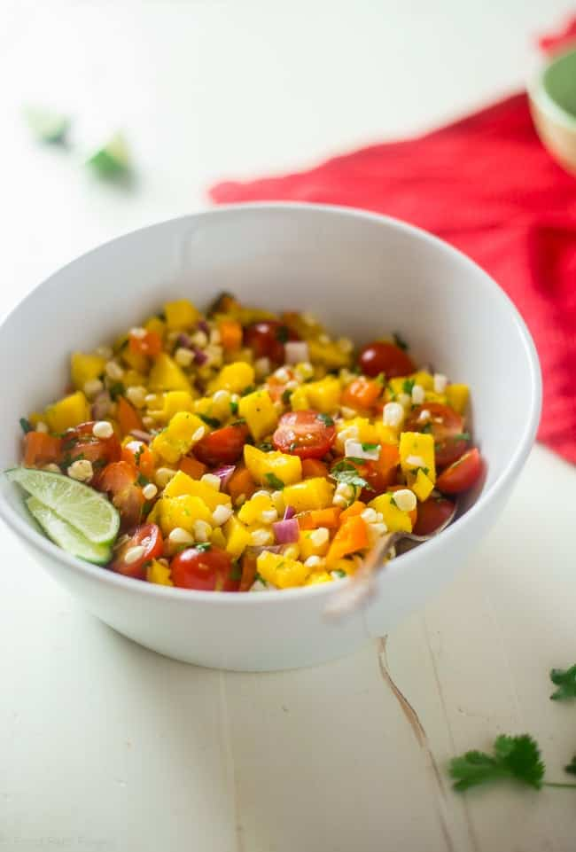 Vegan Fresh Corn and Mango Salad - This healthy salad has fresh corn, juicy, sweet mangos and tons of crispy, fresh vegetables! It's the perfect, quick and easy side dish for summer that is under 100 calories! | Foodfaithfitness.com | @FoodFaithFit