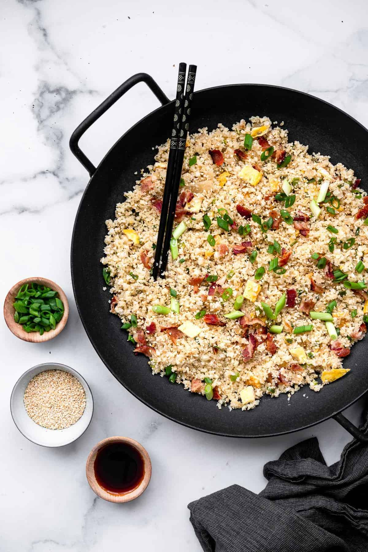 paleo fried rice in a wok with soy sauce on the side