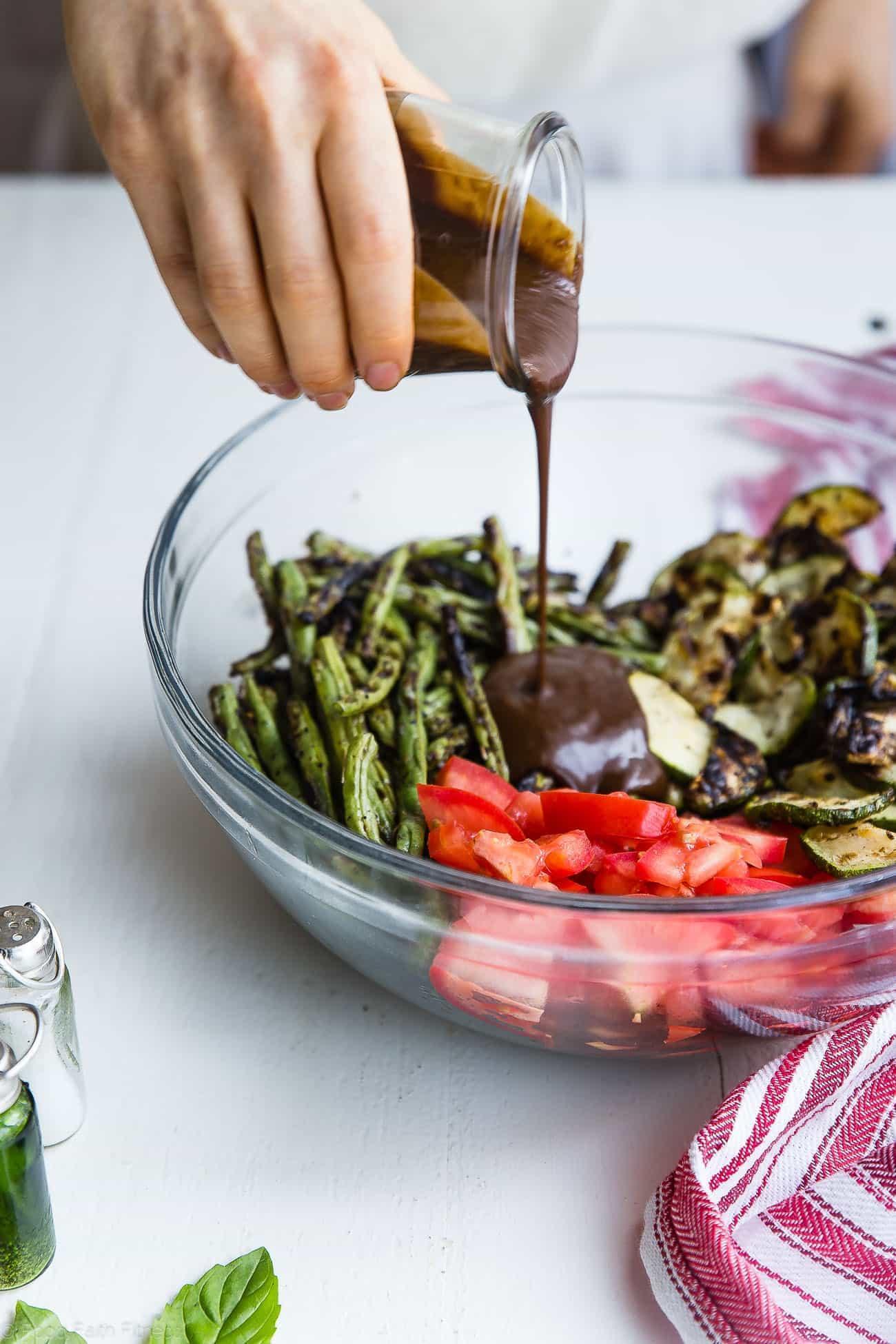 Pouring balsamic vinaigrette on grilled zucchini and green bean salad. Recipe on Foodfaithfitness.com